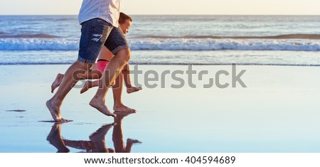 Barefoot legs in action. Happy family fun - parents with baby son running along edge of sea beach surf with sunset light. Active travel lifestyle, water activity and game on summer vacation with child - stock photo