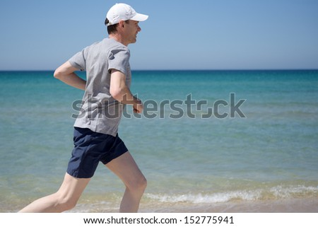 Barefoot man jogging on a beach - stock photo