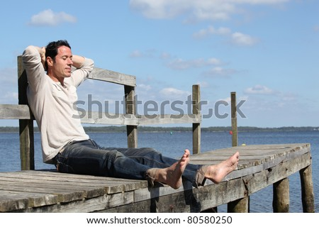 Barefoot man sitting on a wooden jetty enjoying the sunshine - stock photo