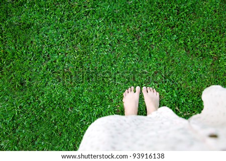 Barefoot of woman on green grass - stock photo