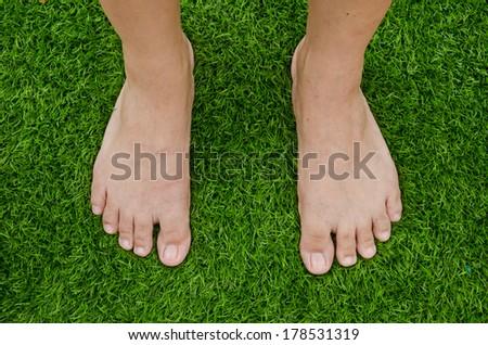 Barefoot on green artificial grass field - stock photo