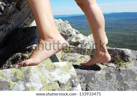 Barefoot step on the rock - stock photo