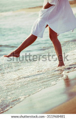 barefoot woman enjoy in sea water in white long shirt, lower body, selective focus, side view - stock photo