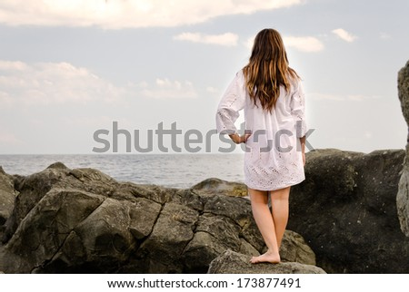 Barefoot woman enjoying the solitude of the seaside as she stands on a rocky shoreline gazing out over a calm ocean in meditation, with copyspace - stock photo