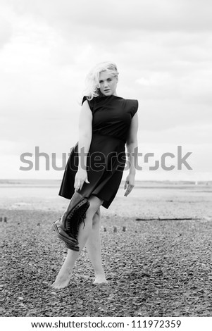 barefoot woman on a stoney beach wearing a dress and holding boots posing