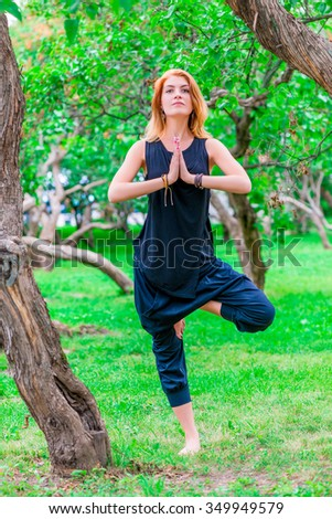 barefoot woman practices yoga in the morning in the park - stock photo