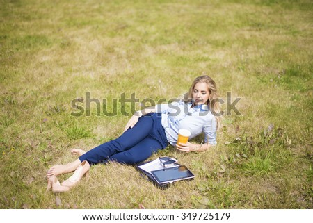 barefoot young adult blond caucasian business Woman drink coffee near tablet computer in park Businesswoman lie on summer fresh green grass outdoor. Water cup and mobile cell phone and document  near - stock photo