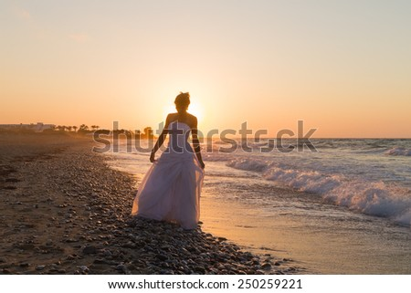 Barefoot young bride in a white wedding dress enjoys a lonesome walk on a wet sandy beach in a late summer hazy day, at dusk. - stock photo