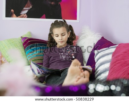 Barefoot Young Girl Reading Magazine, reclining on bed with many pillows - stock photo