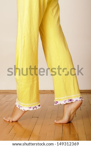 Barefoot young woman in yellow pajamas - stock photo