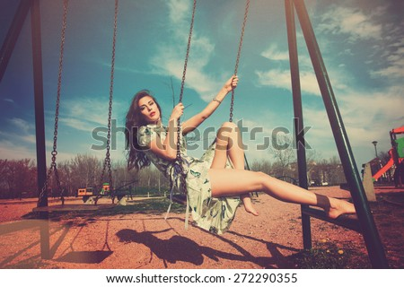 barefoot young woman sit on swing in summer dress in playing park , full body shot, retro colors, color leek texture added - stock photo