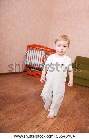 Barefooted boy is walking in his bedroom - stock photo