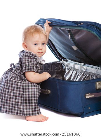 Barefooted kid opening a large suitcase - stock photo