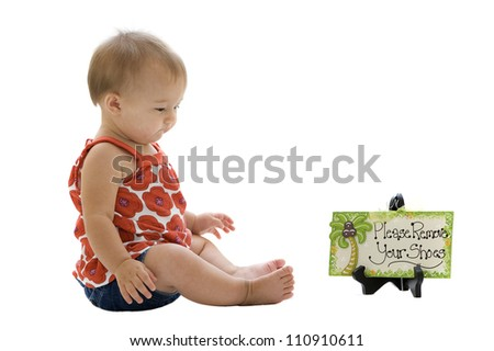 Barefooted little girl sitting by a please remove your shoes sign - stock photo