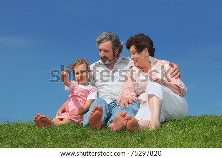 barefooted old man and woman sitting on summer lawn with their granddaughter, girl pointing by finger