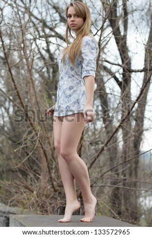 Barefooted pretty blonde wearing white shirt posing like a statue - stock photo