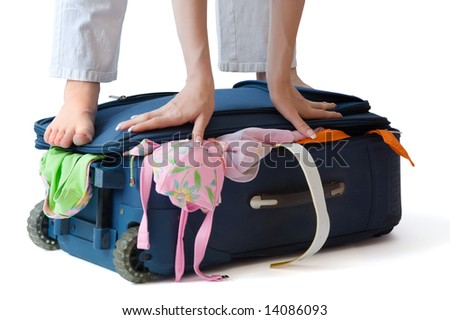 Barefooted woman standing on a suitcase crammed full of clothes, isolated, with clipping path - stock photo