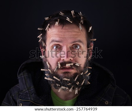 Barely holding it together - stressful bearded man with cloths-pegs holding his head - stock photo