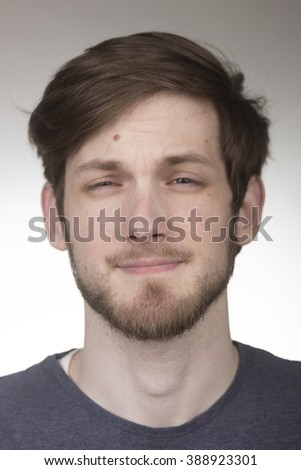 Barely looking, closed eyes, portrait of young caucasian man in 20s. Head and shoulders shot, face close up. Shallow depth of field. - stock photo