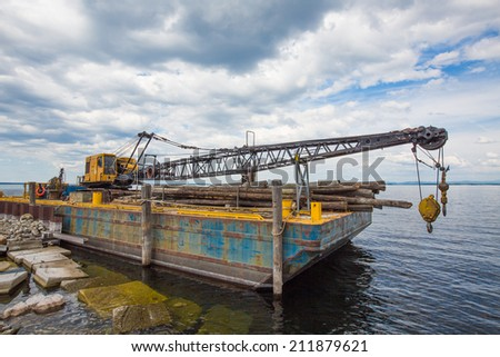 Barge And Crane: carrying wood logs - stock photo