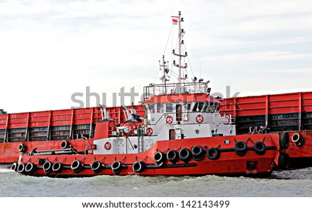 Barge being positioned by tug boat in Cilegon, Indonesia - stock photo