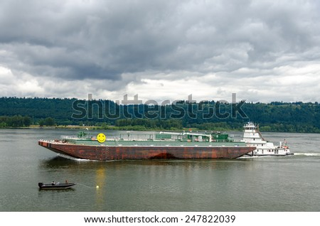 Barge being pushed past a small boat and fisherman - stock photo