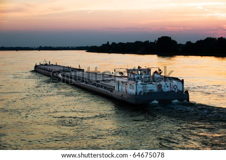 barge in Danube river, at evening sky - stock photo