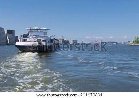 barge on the amsterdam IJ heading towards the North Sea - stock photo