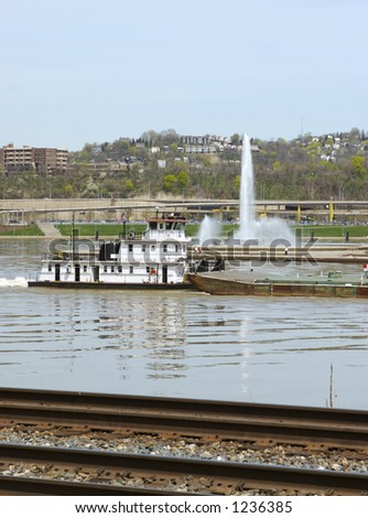 Barge passing by Pittsburgh's Point Fountain with Train Tracks in Foreground - stock photo