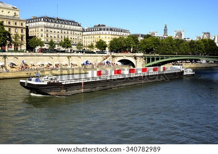 Barge passing over the Seine, along the banks people spend the summer in Paris. - stock photo