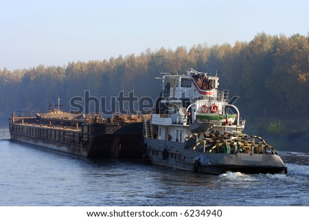 Barge pushed by towboat on the river. - stock photo
