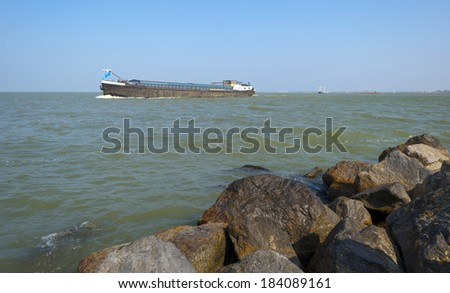 Barge sailing on the horizon of a lake in spring