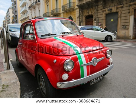 BARI, ITALY - MARCH 16, 2015: A red version of the iconic Fiat 500 with the Italian flag in the center of Bari, Italy.