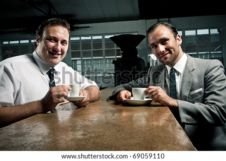 Barista and suit man pose for a picture together - stock photo