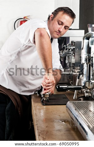 Barista compresses coffee grounds with tamper until nice and level - stock photo