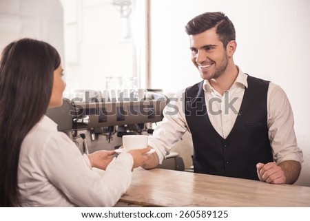 Barista giving cup of coffee  to woman at counter in the coffee shop. - stock photo
