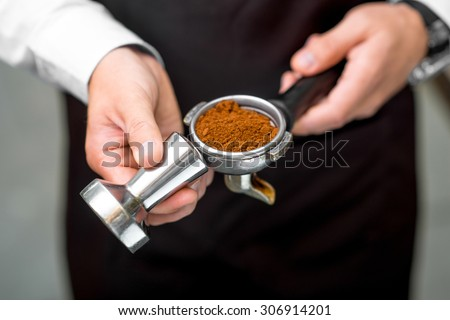 Barista holding coffee machine holder filled with coffee on the brown apron background. Close up view focused on the coffee - stock photo