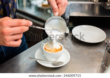 Barista in cafe or coffee bar preparing proper cappuccino pouring milk froth in a cup - stock photo