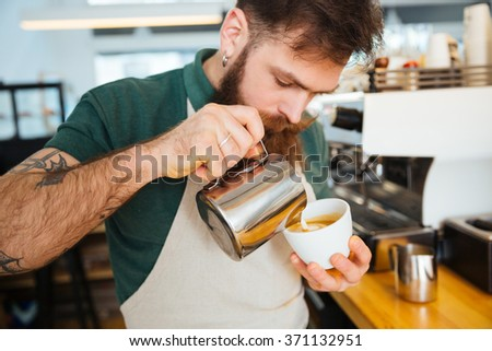 Barista making cappuccino in coffee shop - stock photo