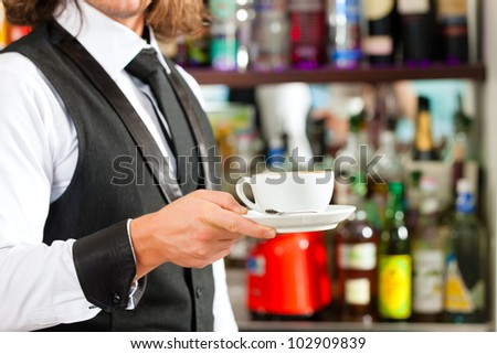 Barista making cappuccino in his coffeeshop or cafe - stock photo