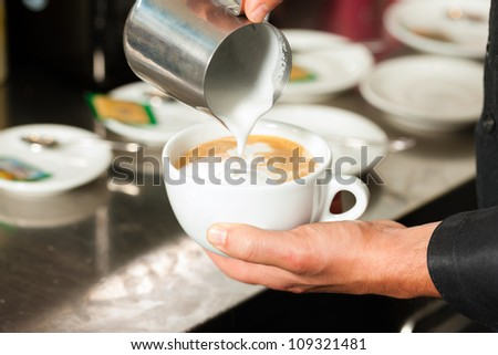 Barista making cappuccino in his coffeeshop or cafe, close-up - stock photo