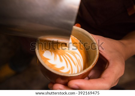 Barista making coffee with latte art.
