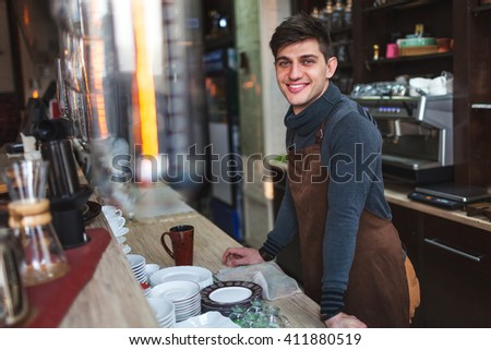 barista man portrait behind the bar in cafe - stock photo