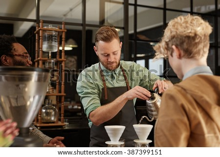 Barista pouring fresh coffee through filter in modern cafe - stock photo
