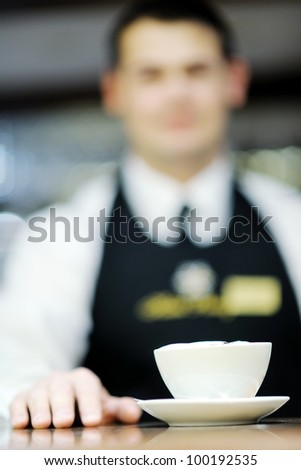 Barista prepares cappuccino in his coffee shop - stock photo