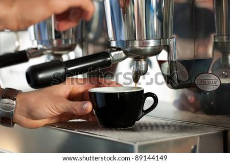Barista prepares cappuccino in his coffee shop; close-up - stock photo