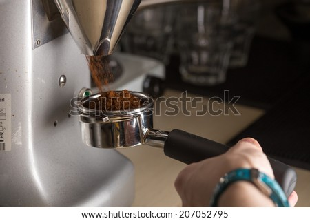 Barista prepares espresso coffee in coffeeshop - stock photo