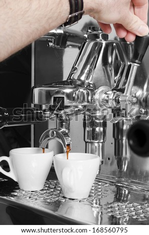 Barista prepares espresso in his coffeeshop; close-up - stock photo