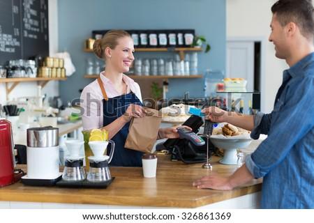 Barista serving customer in coffee shop  - stock photo