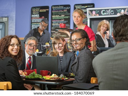 Barista serving diverse group of smiling business people - stock photo